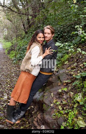 Woman leaning on man against a rock. - Stock-Bilder