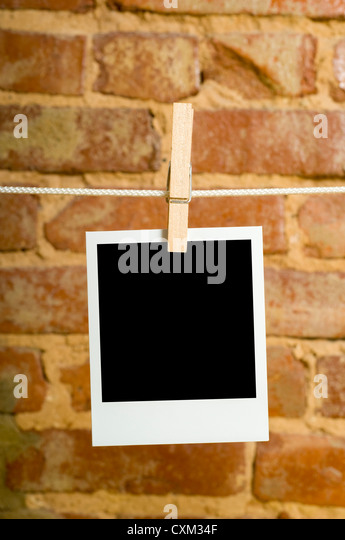 Instant transfer images or Polaroids on a clothesline in front of a brick wall with clipping path for image area - Stock Image
