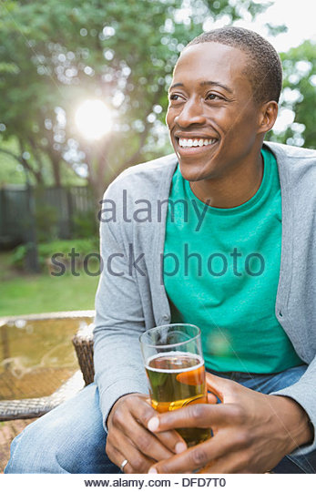 Smiling man relaxing with a drink in backyard - Stock Image