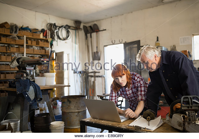 Father and daughter working on laptop in workshop - Stock-Bilder