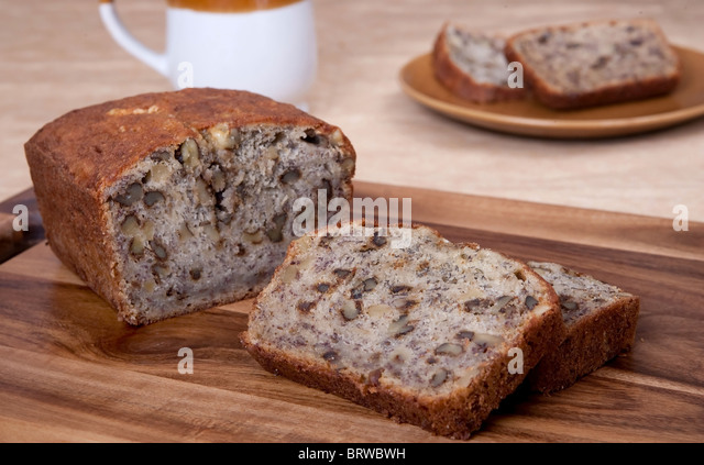 sliced loaf of banana walnut bread on a cutting board with one serving of two slices and a mug in the background - Stock-Bilder