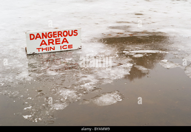 A pond covered in a thin layer of ice with some open water, and a sign signifying the danger. - Stock Image
