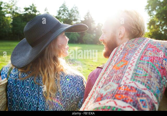 Rear view of romantic young couple carrying rug for picnic in park - Stock-Bilder