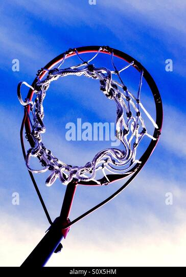 Looking up at a basketball net towards a blue sky. - Stock Image
