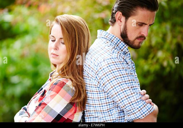 Couple stood back to back - Stock Image