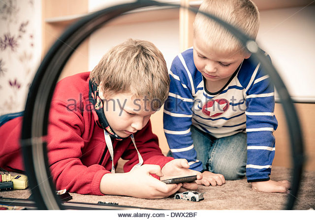Siblings playing video game at home - Stock Image