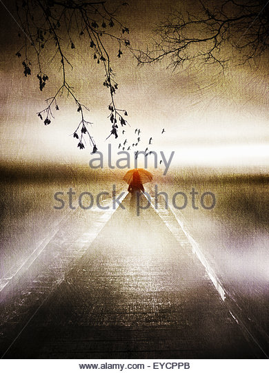 Solitary woman with red umbrella on atmospheric jetty - Stock Image