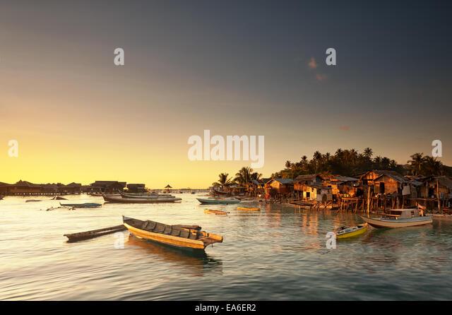 Malaysia, Sabah, Small boats and Sea Gypsy huts at sunrise - Stock Image