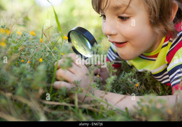 Happy little boy looking through magnifying glass - Stock-Bilder