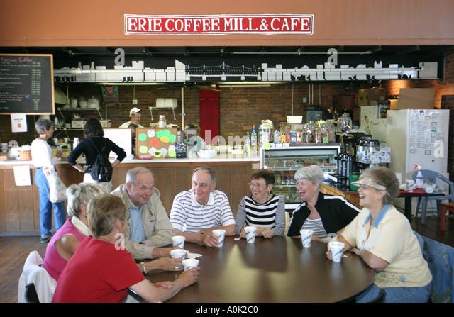 Toledo Ohio Erie Street Market Erie Coffee Mill and Cafe seniors men women drinking talking - Stock Image