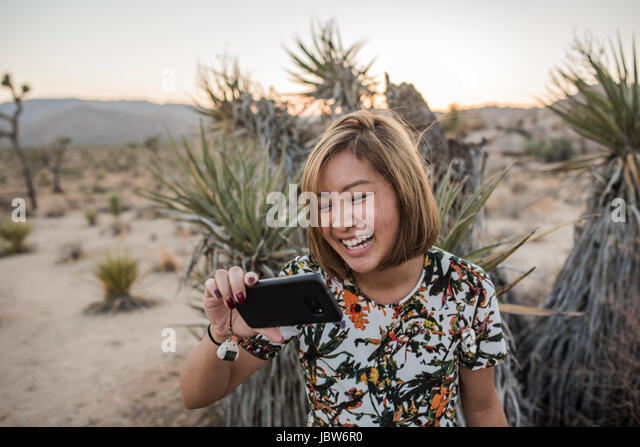 Young woman taking smartphone selfie in Joshua Tree National Park at dusk, California, USA - Stock-Bilder