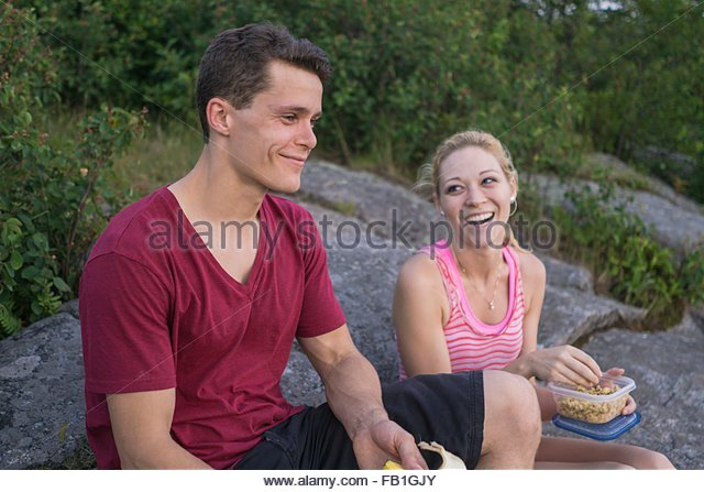 Young couple sitting on rocks in forest, eating packed lunch - Stock Image