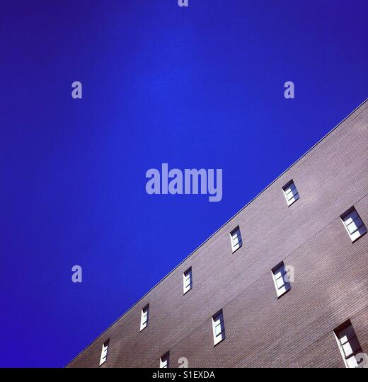 An older brick building against a clear blue sky - Stock Image