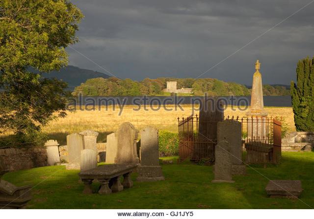 The view across Kirkgate graveyard to Lochleven Castle, Loch Leven, Kinross, Perthshire, Scotland - Stock Image