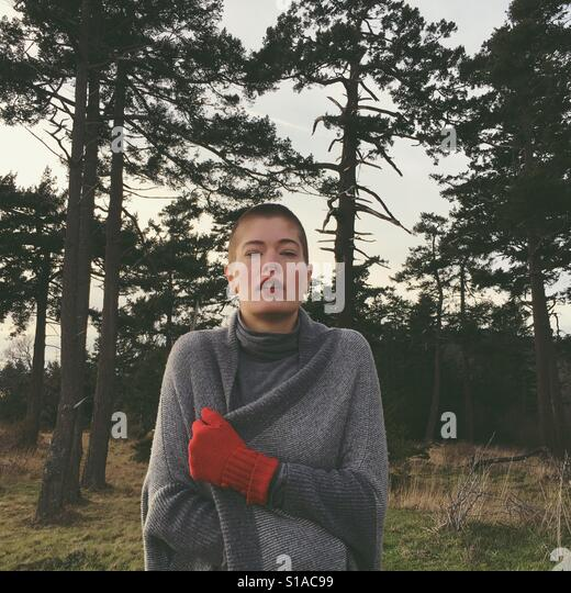 Cold woman with grey shawl and red gloves with buzz cut shaved head on forest path - Stock-Bilder