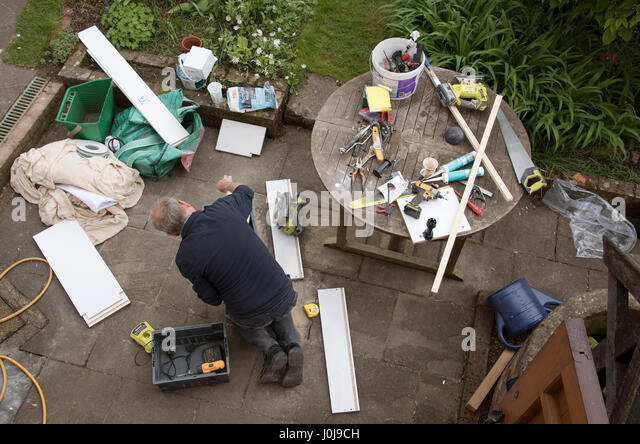 An overview of a handyman engaged in some DIY work on the garden patio - Stock Image