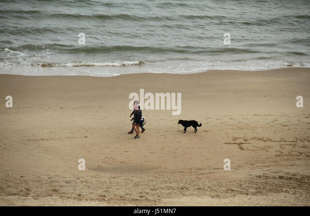 Bournemouth, UK -  11 May: A couple with their dog seen walking on the sandy Bournemouth beach. General view of - Stock Image
