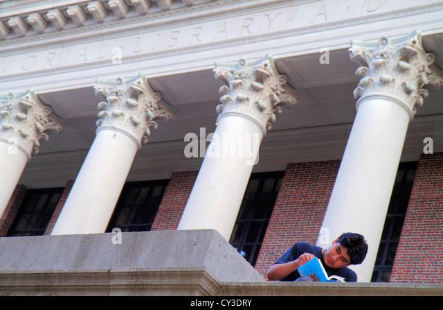 Boston Massachusetts Cambridge Harvard University campus Asian man student sitting Widener Library front entrance - Stock Image
