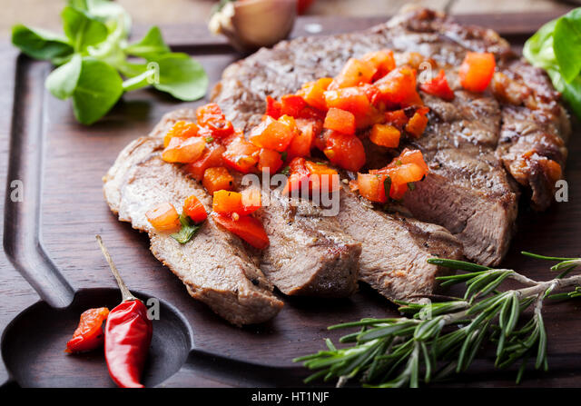 Beef steak well done with tomato and pepper salsa on a wooden background. - Stock Image