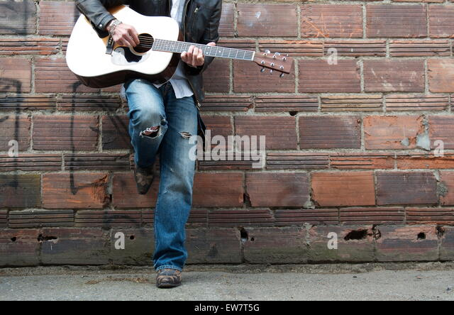 Man in Leather Jacket and Cowboy Boots Playing the Guitar in an Alley - Stock Image