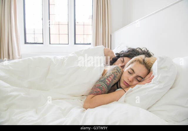 A cool young tattooed couple sleeping in a bed. - Stock Image