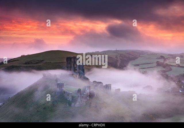 The ruins of Corfe Castle rising through the morning mist. - Stock Image