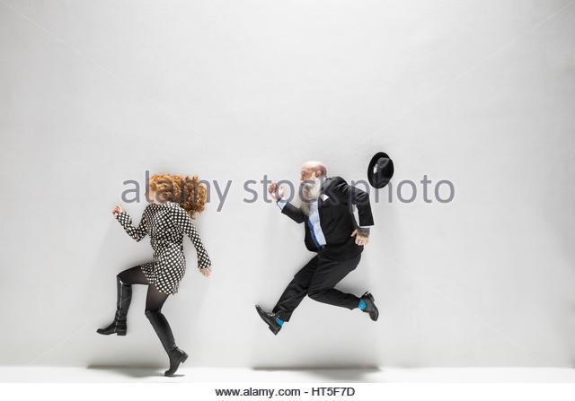 Businessman chasing businesswoman against white background - Stock-Bilder