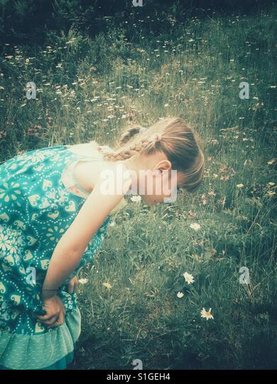 Cute little girl smelling the wild flowers with grainy vintage filter for a retro vibe of summer childhood. - Stock-Bilder