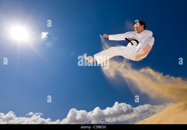 Black belt martial artist in flying attack. - Stock Image