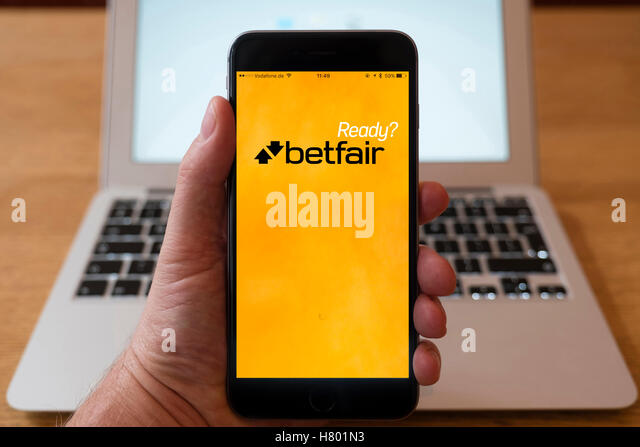 Using iPhone smartphone to display homepage logo of Betfair gambling app - Stock Image