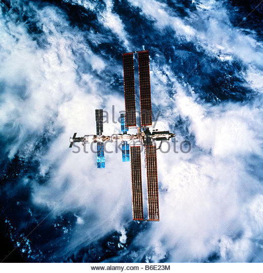 International Space Station (ISS) orbiting above the Earth. Blue and brown solar panels extend out from the ISS. - Stock Image