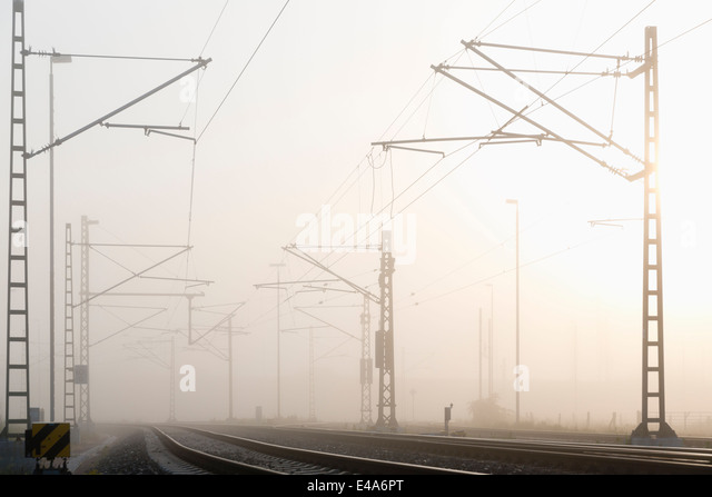Germany, Hamburg, railway track in early morning fog - Stock Image