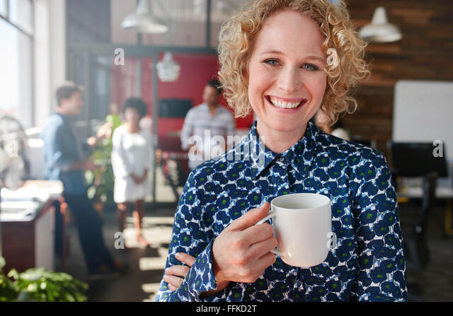 Portrait of cheerful female designer holding a cup of coffee. She is standing in office with colleagues discussing - Stock Image