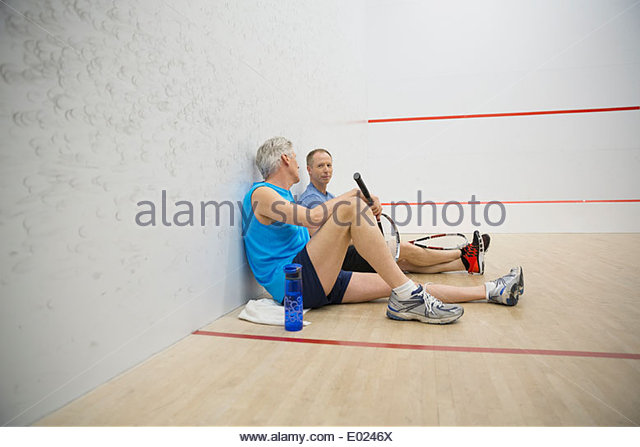 Men talking on squash court - Stock Image