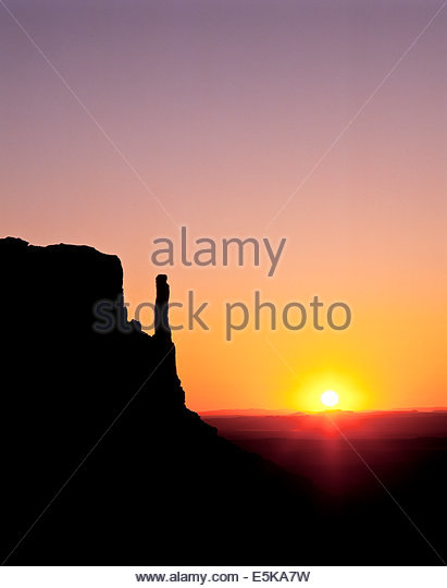 Sunrise behind the west mitten butte in Monument Valley, a Navajo Tribal Park on the Navajo reservation in Arizona - Stock Image