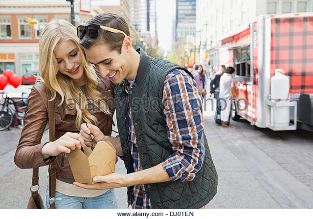 Couple standing outdoors sharing a meal from a food truck - Stock Image
