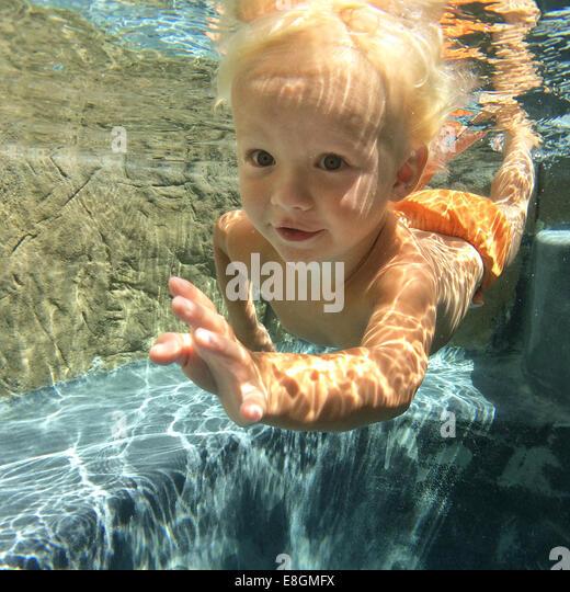 Boy swimming underwater - Stock Image
