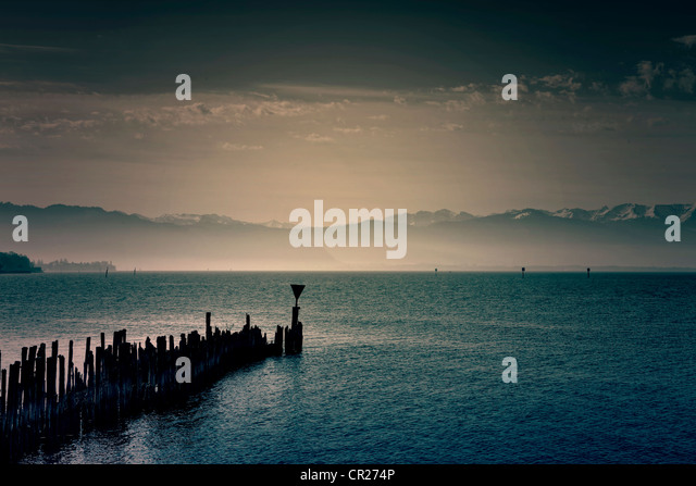 an old breakwater of wooden piles juts out into a lake - Stock Image