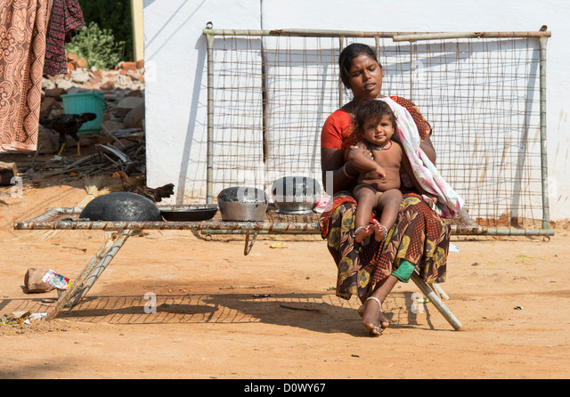 Young Indian woman drying her baby girl after bathing in a rural indian village. Andhra Pradesh, India - Stock Image