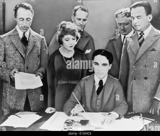 DW Griffith, Mary Pickford, Charlie Chaplin, Douglas Fairbanks signing contract establishing United Artists motion - Stock Image