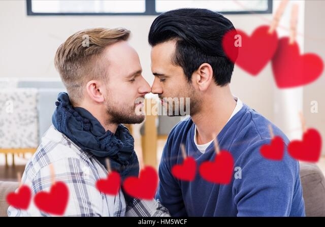 Composite image of red hanging heart and homosexual couple kissing - Stock-Bilder