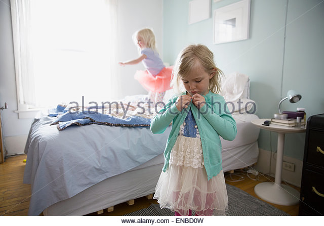 Girl buttoning sweater in bedroom - Stock Image