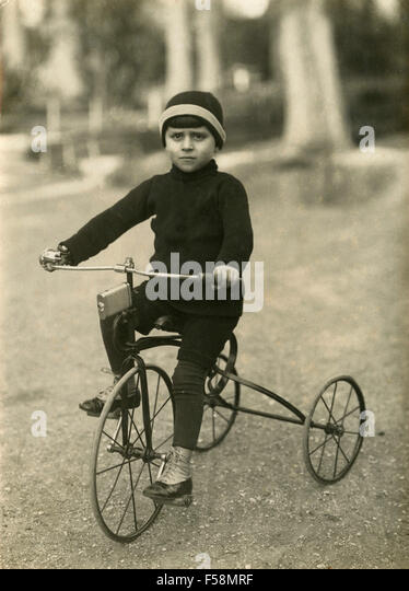 Child on a tricycle, Italy - Stock Image