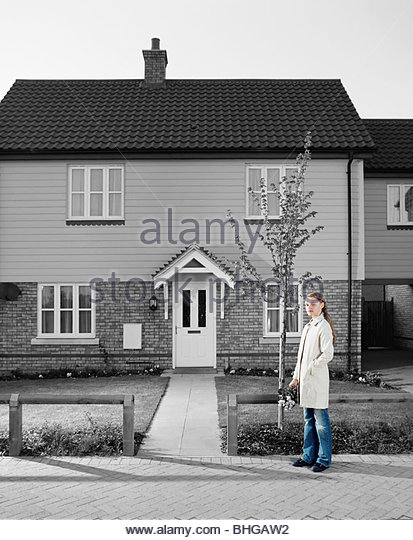 Young woman outside house - Stock Image