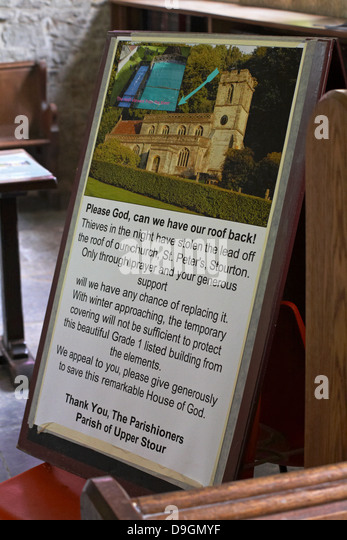 Please God can we have our roof back notice board in church of St Peter's at Stourton, Wiltshire in June - Stock Image