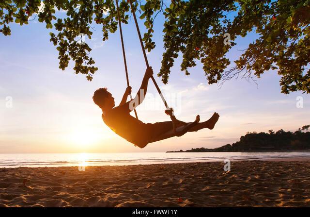 swing on paradise tropical beach at sunset, happy people enjoying summer - Stock Image