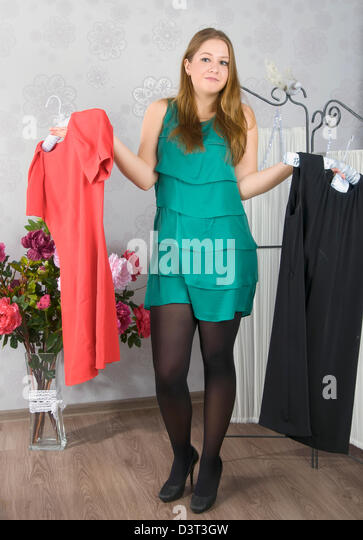 Girl chooses one of the three dresses - Stock Image