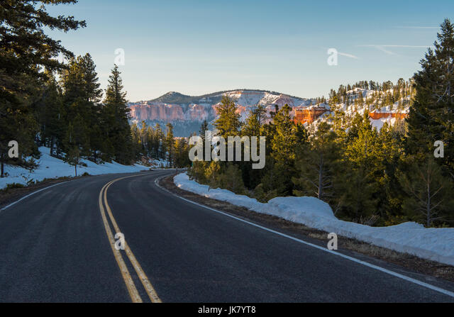 Snowy Mountain Road with Bright Orange Rocks in Background - Stock Image