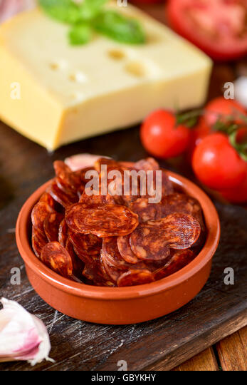 closeup of an earthenware bowl with some slices of Spanish chorizo, a pork sausage typical of Spain, on a rustic - Stock Image