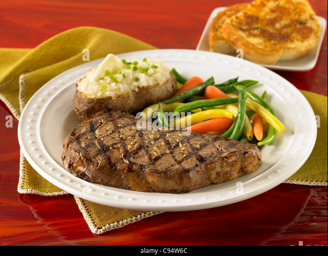 Rib eye steak served with a loaded baked potato, vegetables and garlic bread - Stock Image
